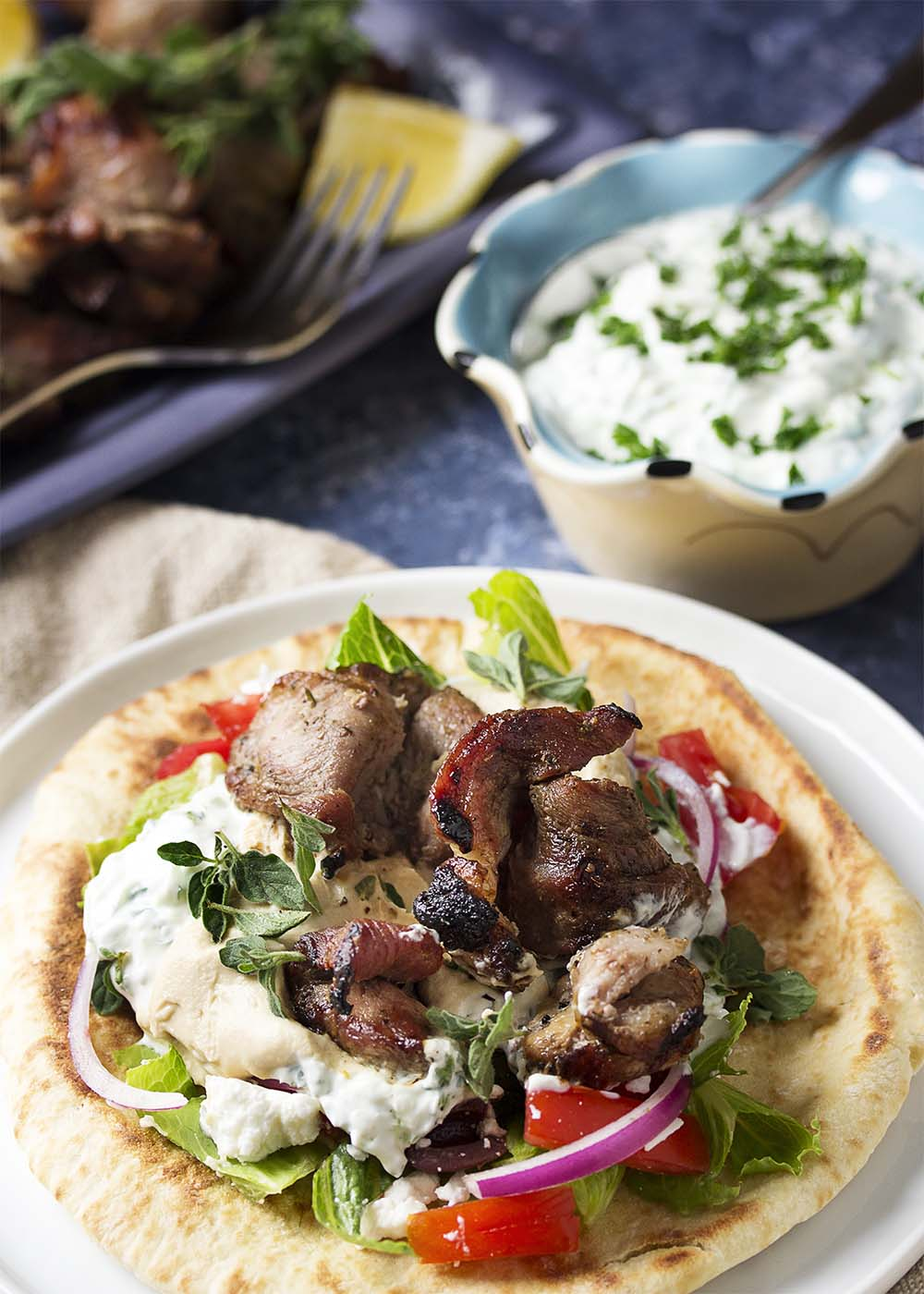 Grilled pork souvlaki on a pita with tzatziki sauce, hummus, lettuce, and tomatoes to make a gyro sandwich.