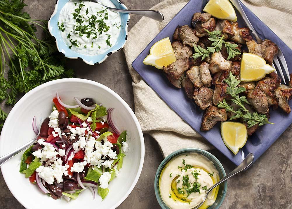 A table set with a platter of grilled pork souvlaki, Greek salad, tzatziki sauce, and hummus.