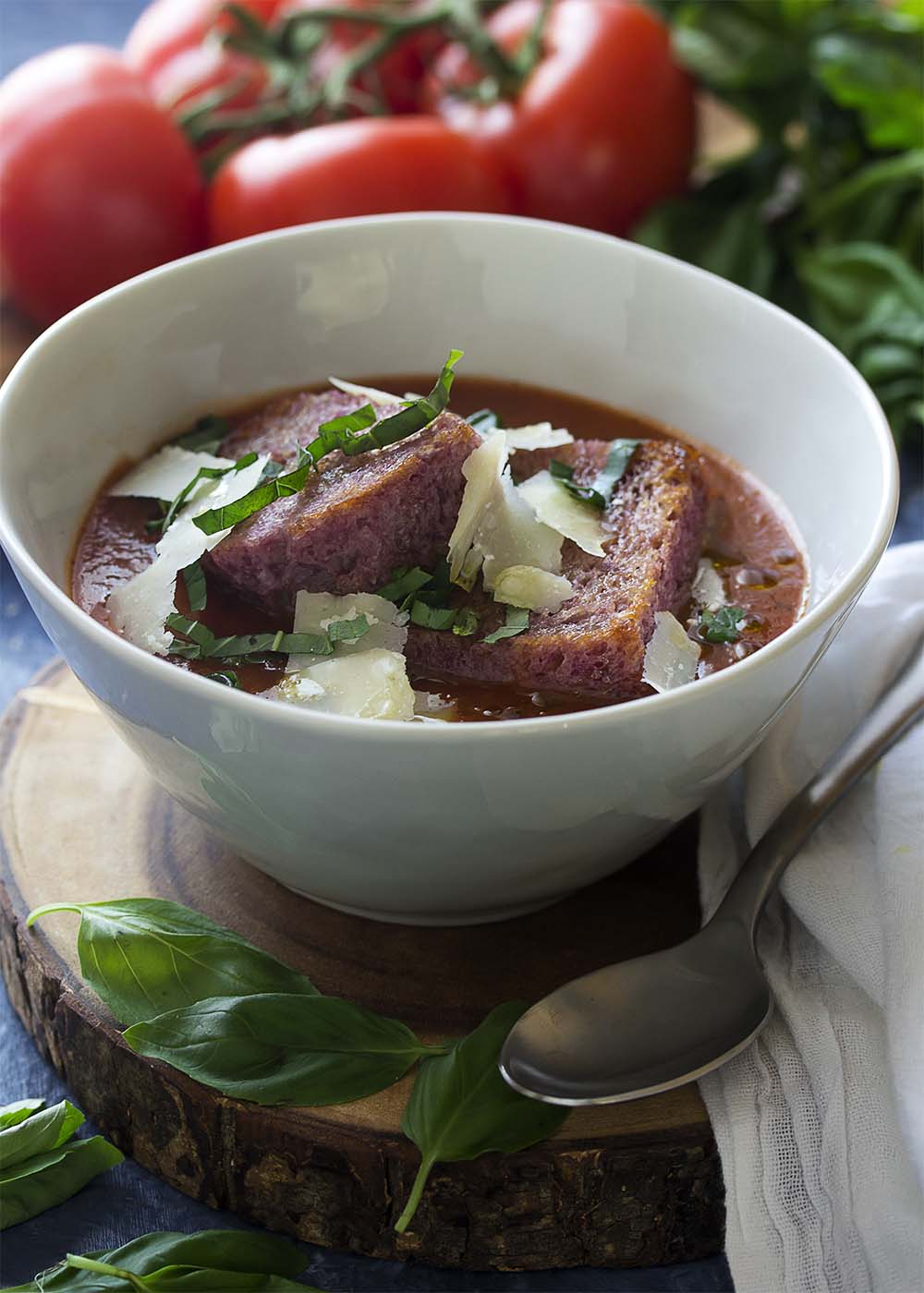 A bowl of tomato basil soup with a spoon topped with basil, parmesan, and red wine croutons.