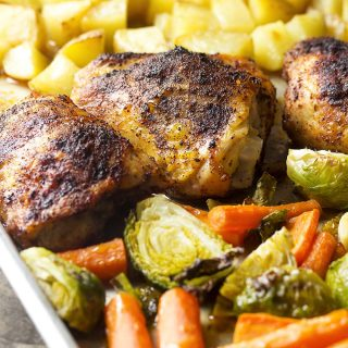 For an easy dinner, make sheet pan chicken with vegetables and potatoes! Juicy chicken thighs, roasted veggies like Brussels sprouts, carrots, and diced potatoes make for a complete meal in one pan. | justalittlebitofbacon.com #sheetpan #chickenrecipes #chickendinner #onepanmeal #chicken