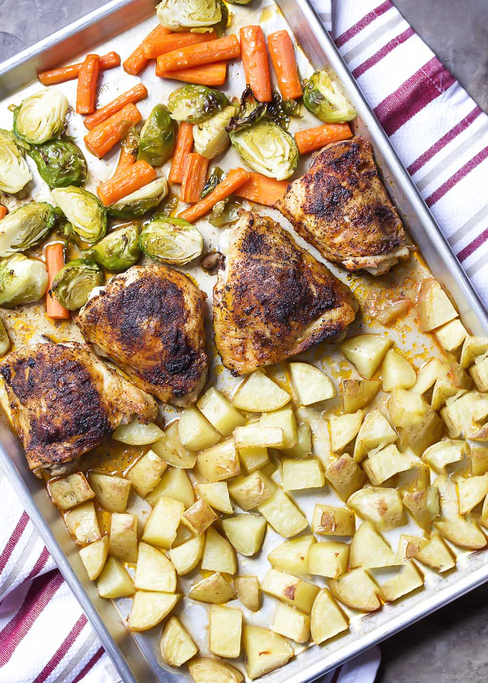 Top view of the sheet pan with the chicken, vegetables, and potatoes arranged for baking.