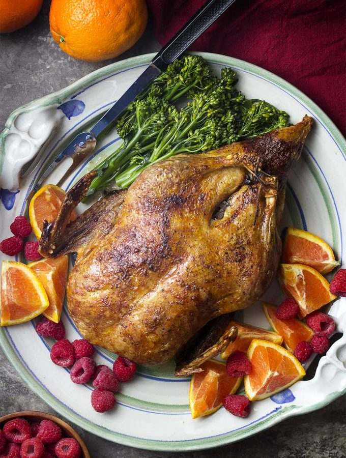 Crispy slow roasted duck is served with a raspberry orange port sauce. It's a simple, yet impressive, dinner recipe perfect for holidays and celebrations. Great for Christmas, Easter, Thanksgiving, and more! | justalittlebitofbacon.com #duckrecipes #holidayrecipes #christmasrecipes #easterrecipes #thanksgivingrecipes