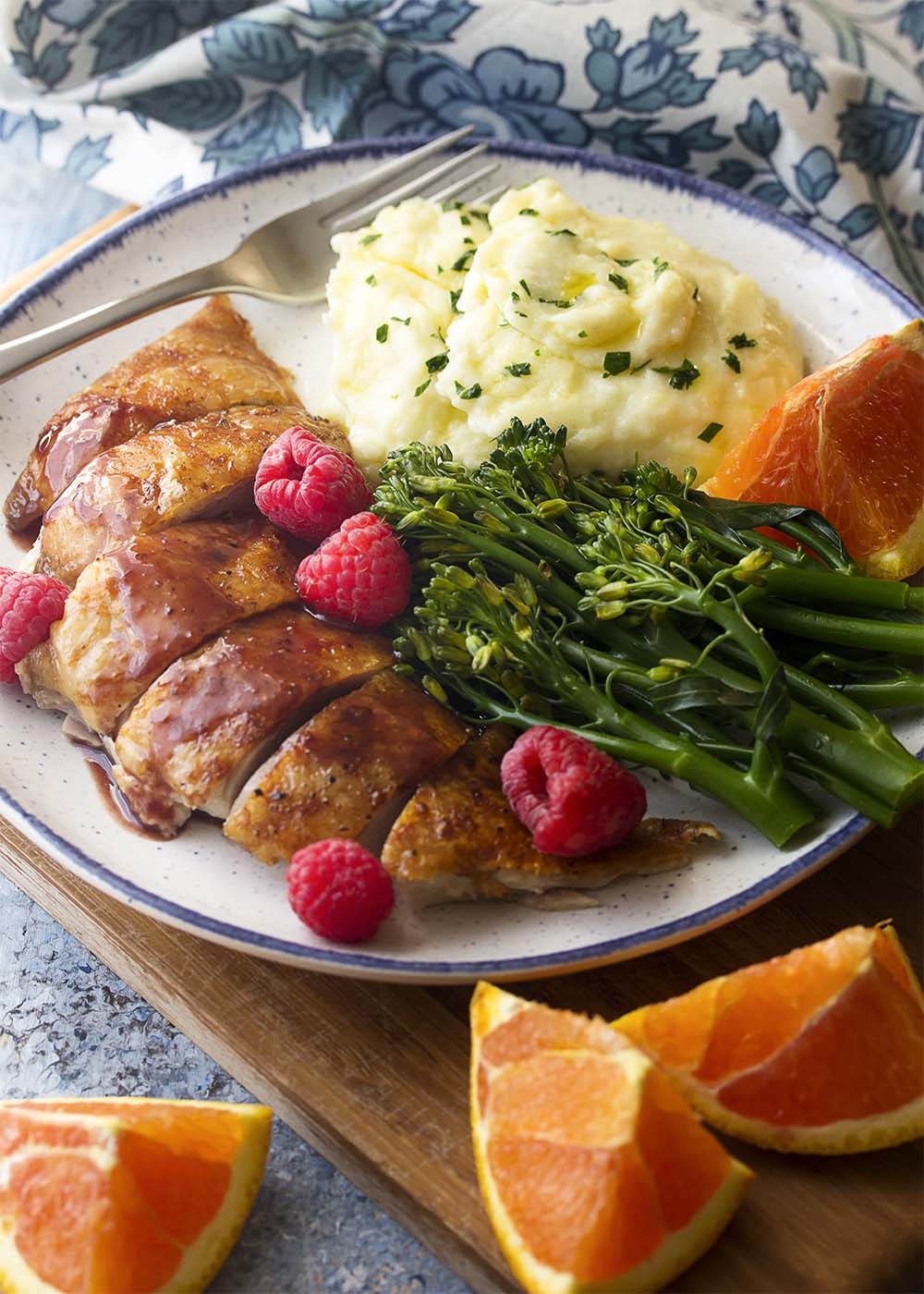 Sliced duck breast on a plate with mashed potatoes, broccolini, oranges, and raspberries.