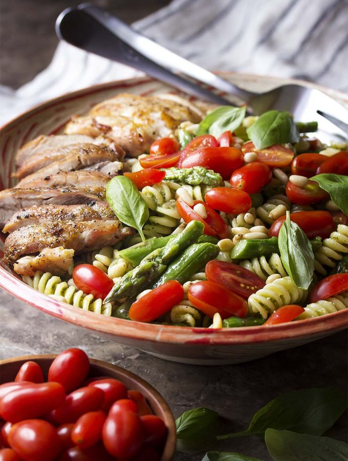 For an easy and healthy cold summer or spring dinner, make chicken pesto pasta salad! It's full of the fresh flavors of tomatoes, basil, and asparagus along with simple grilled chicken thighs. Can be served warm or made ahead for a bbq or picnic. | justalittlebitofbacon.com #saladrecipes #italianrecipes #pastasalad #pesto #summerrecipes #grilledrecipes