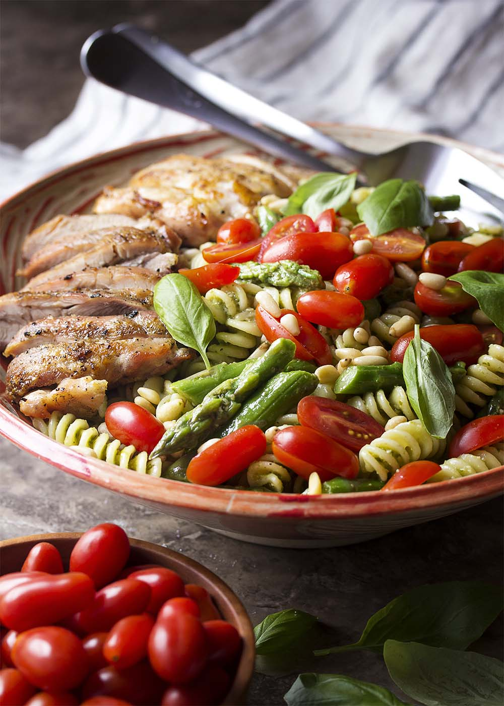 Serving bowl full of fresh and flavorful chicken pesto pasta salad.
