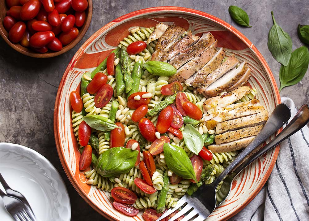 Top view of a serving bowl of cold pesto pasta salad with grilled chicken and asparagus.