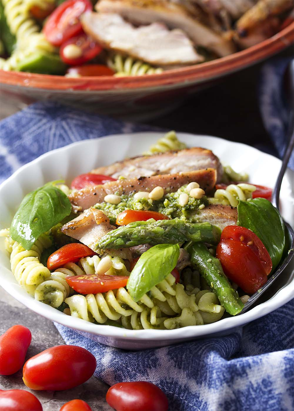 A small bowl of pasta salad with basil pesto, grilled chicken, asparugus, and sliced tomatoes.