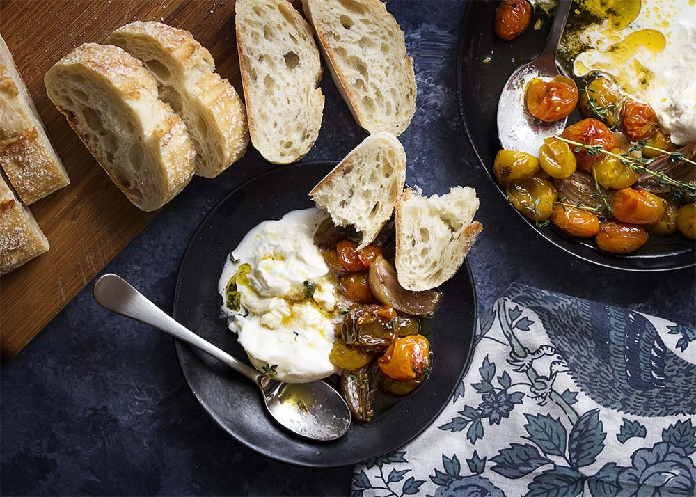 A small black dish of cherry tomato caprese and burrata with crusty bread.
