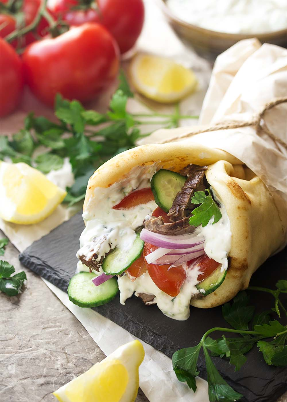 A steak gyro wrap filled with sliced steak, tzatziki sauce, tomatoes, and onions.