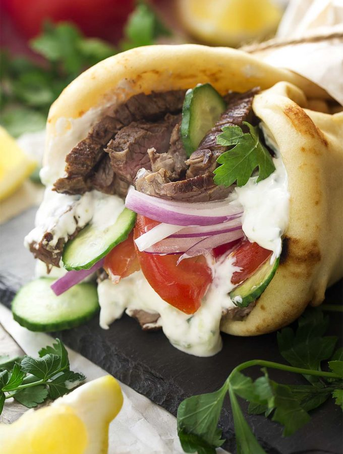 For a great beef dinner with Greek flavors make grilled skirt steak gyros tonight! A quick marinade and homemade tzatziki sauce along with a few toppings and some pita bread are all you need. | justalittlebitofbacon.com #greekrecipes #gyros #beefrecipes #grillingrecipes #greek #skirtsteak