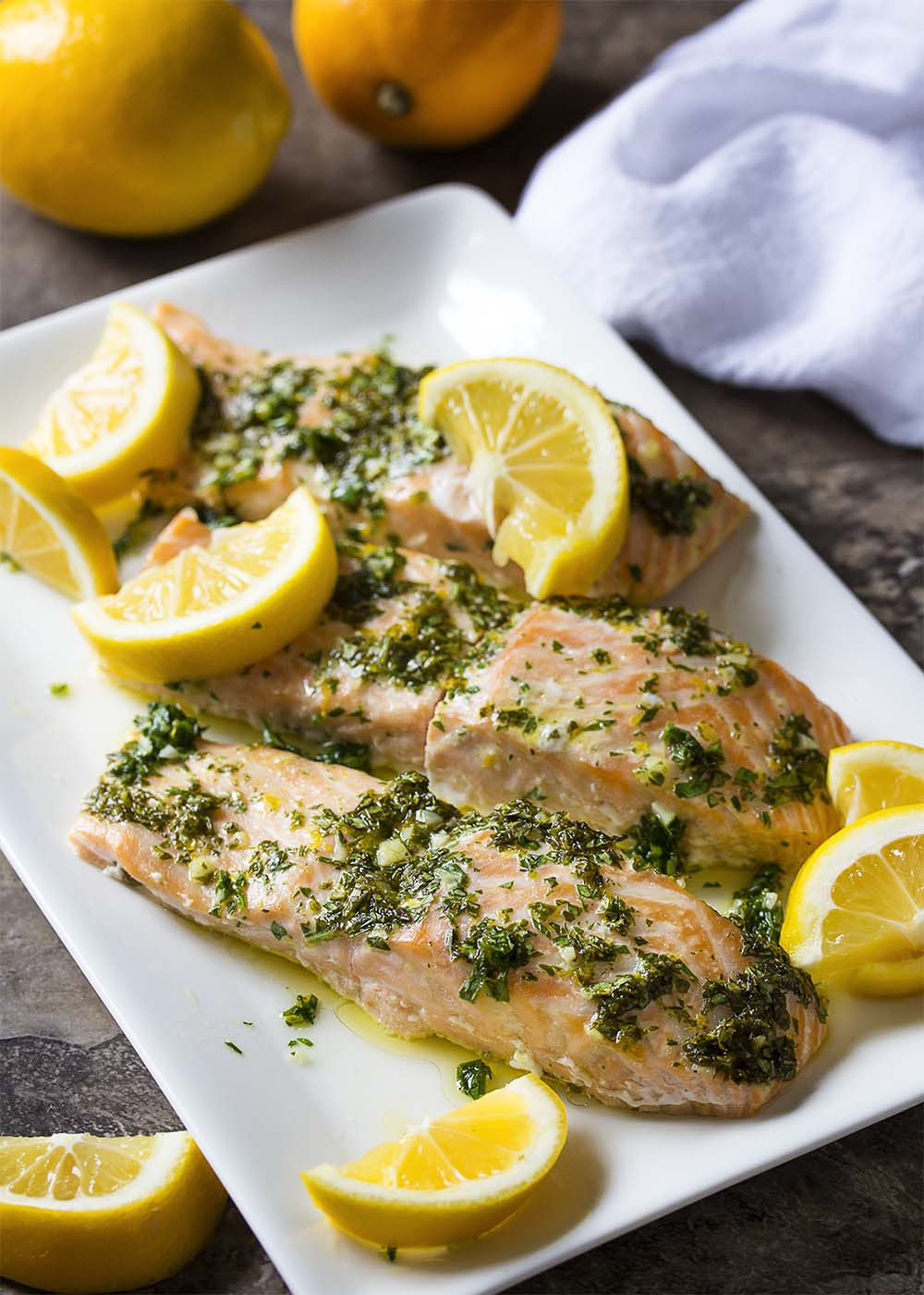A plate of slow roasted salmon fillets topped with a lemon herb sauce and lemon slices.