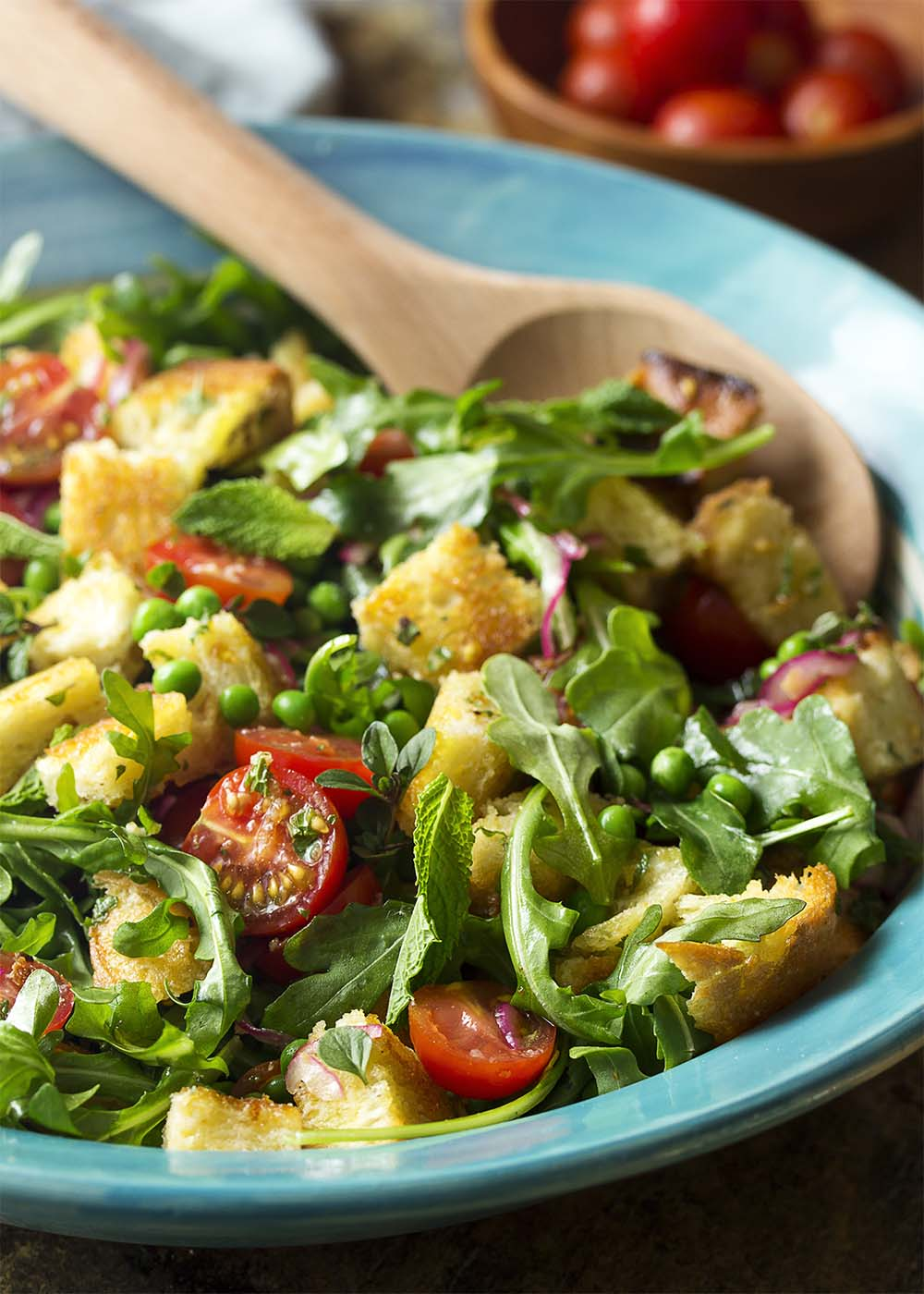 A serving bowl of salad full of toasted bread, arugula, tomatoes, peas, and mint.