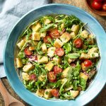 For a fresh take on Italian bread salad, make a spring panzanella salad with peas, arugula, mint, and cherry tomatoes all tossed in a bright, lemony dressing. | justalittlebitofbacon.com #saladrecipes #italianrecipes #panzanella #tomatobreadsalad #springrecipes