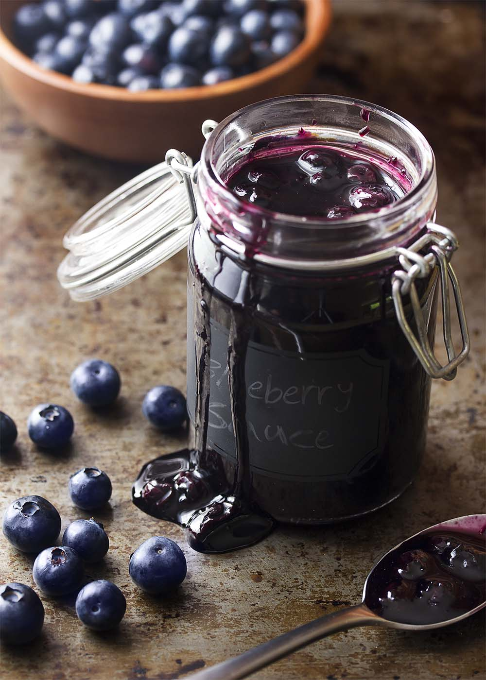Fresh blueberry sauce in a mason jar with the cap off showing the sauce inside.