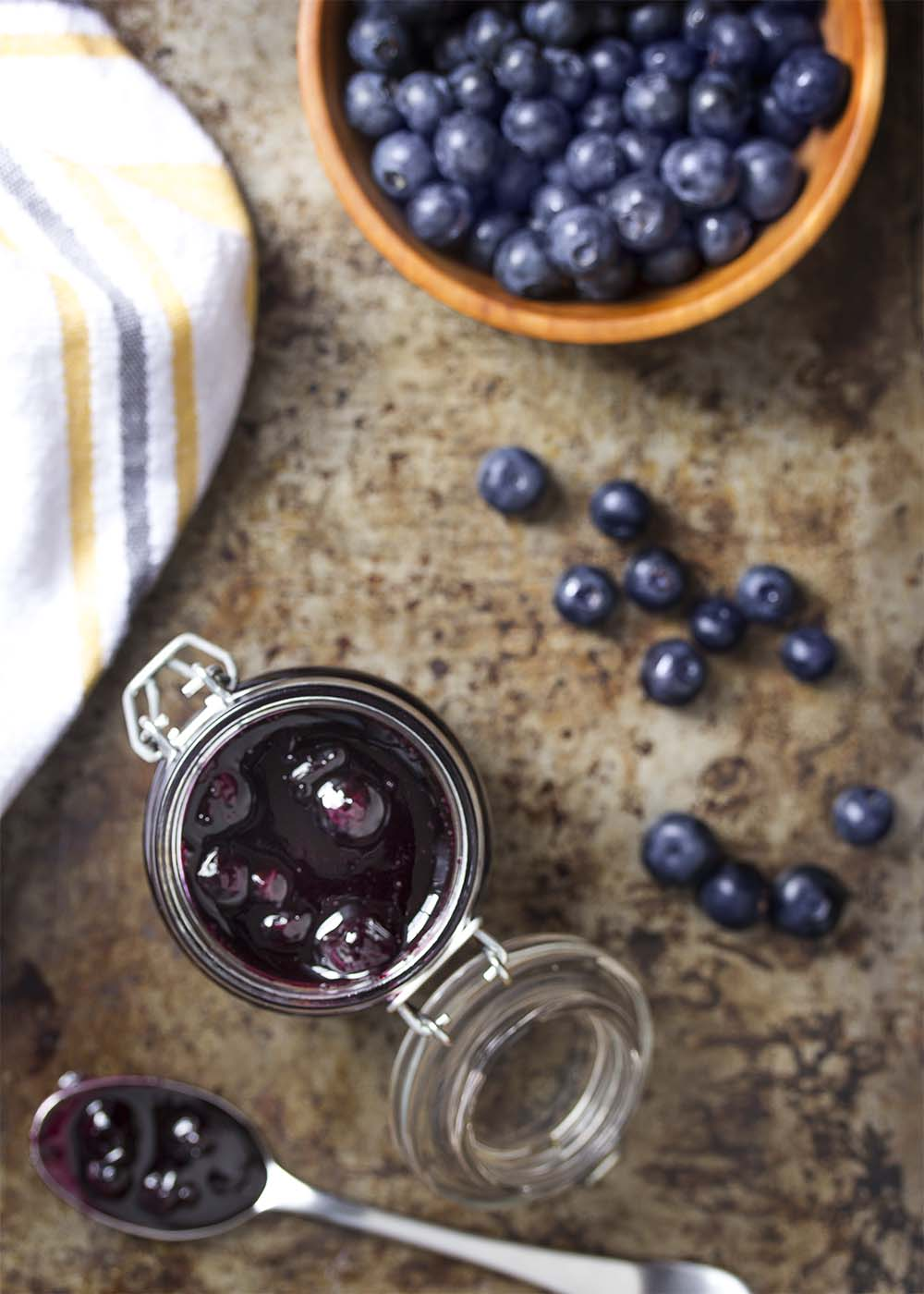 Top view of blueberry sauce in a mason jar. A spoon of sauce on the table.