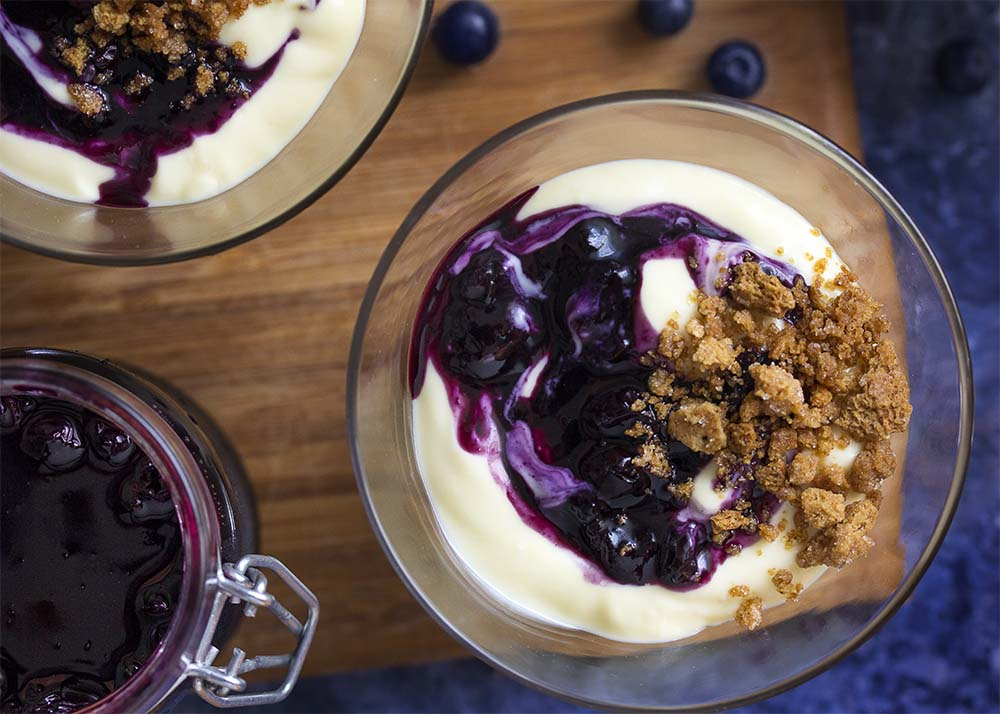 Top view of glasses with fresh blueberry sauce spooned over cheesecake pudding with graham cracker crumbs.