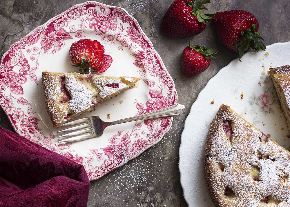 A slice of strawberry walnut cake on a plate with a fork and a dusting of confectioners' sugar.