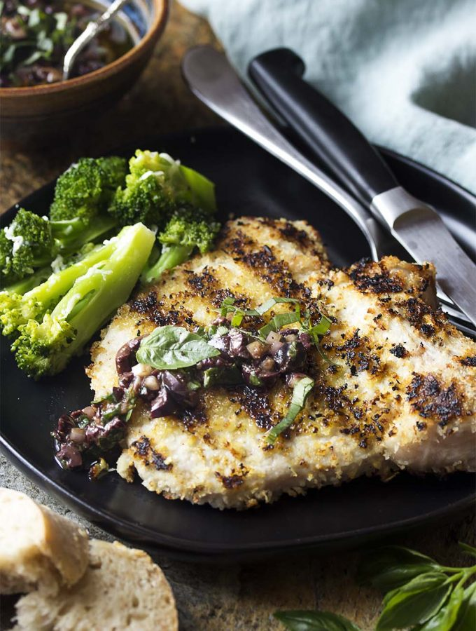 My bone-in grilled breaded pork chops are pounded thin and covered in a panko and parmesan crust for a tender and juicy Italian style summer dinner. Serve with a simple sauce of black olives and basil. | justalittlebitofbacon.com #grillrecipes #summerrecipes #italianrecipes #porkrecipes #porkchops #italian #dinnerrecipes