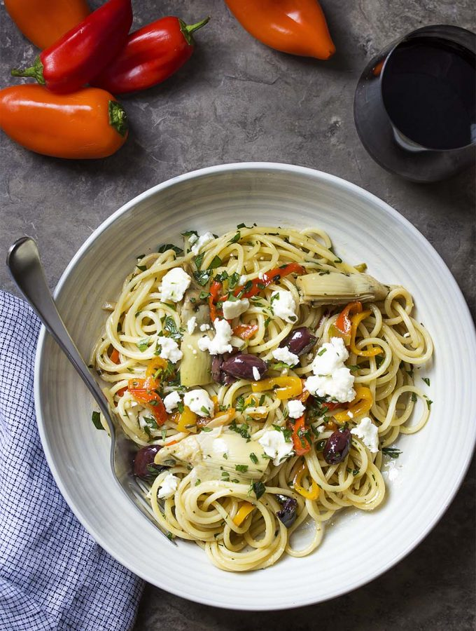 Looking for some healthy weeknight comfort food? In this recipe for vegetarian Mediterranean pasta, toss spaghetti with sliced red peppers, feta, artichokes, and kalamata olives for an easy dinner full of great flavors and tasty veggies! | justalittlebitofbacon.com #mediterraneandiet #mediterraneanrecipes #greekrecipes #pastarecipes #vegetarian #vegetarianpasta