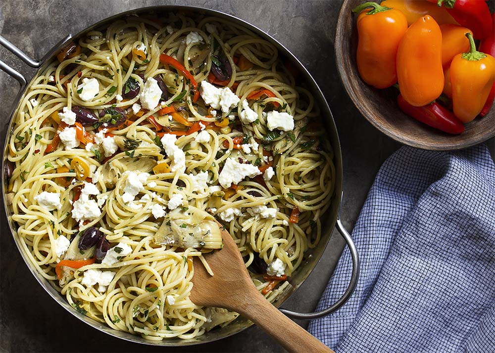 Top view of a skillet full of spaghetti mixed with vegetables and cheese.