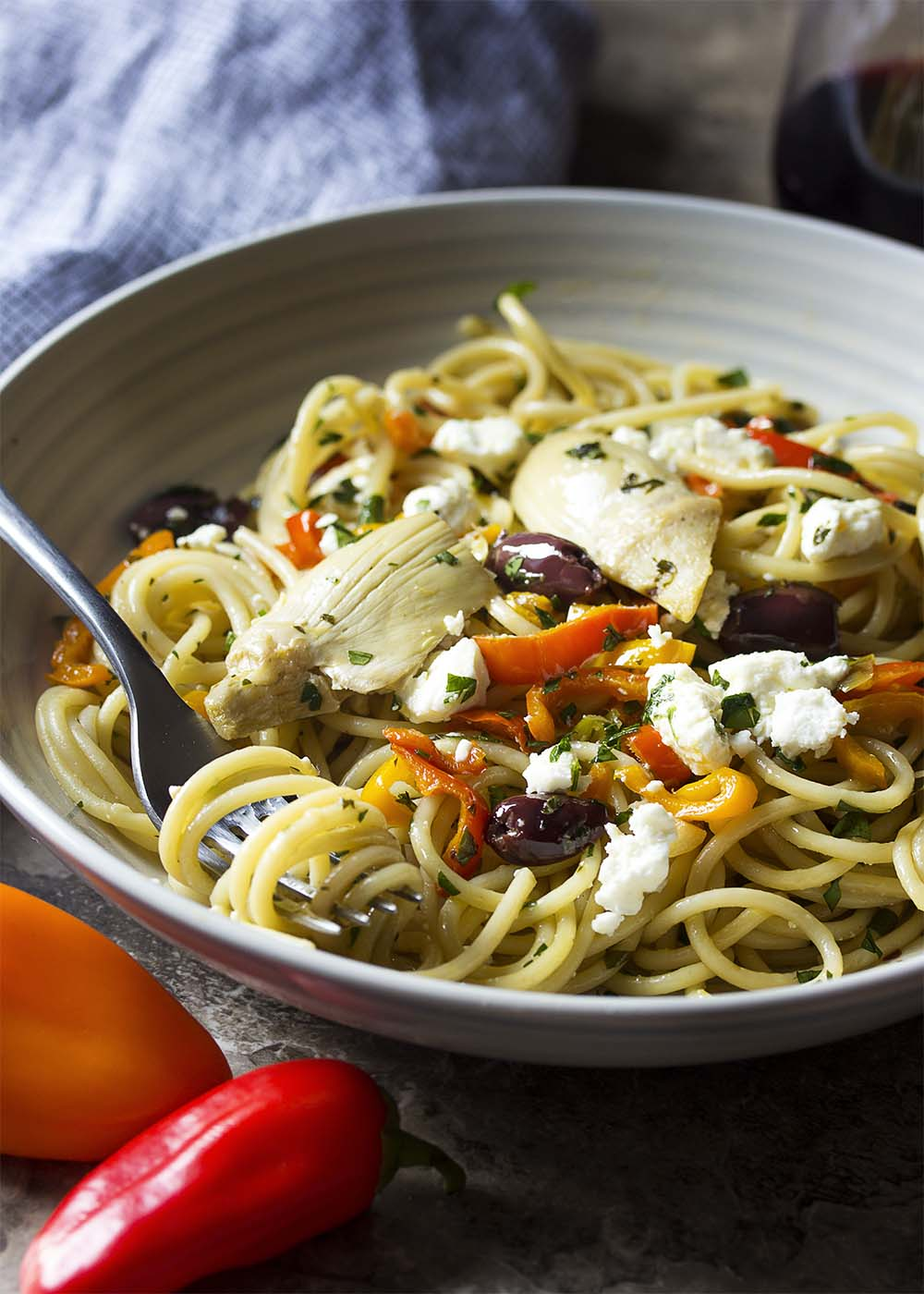 A bowl of vegetarian Mediterrean pasta with artichokes, bell peppers, black olives, and feta.