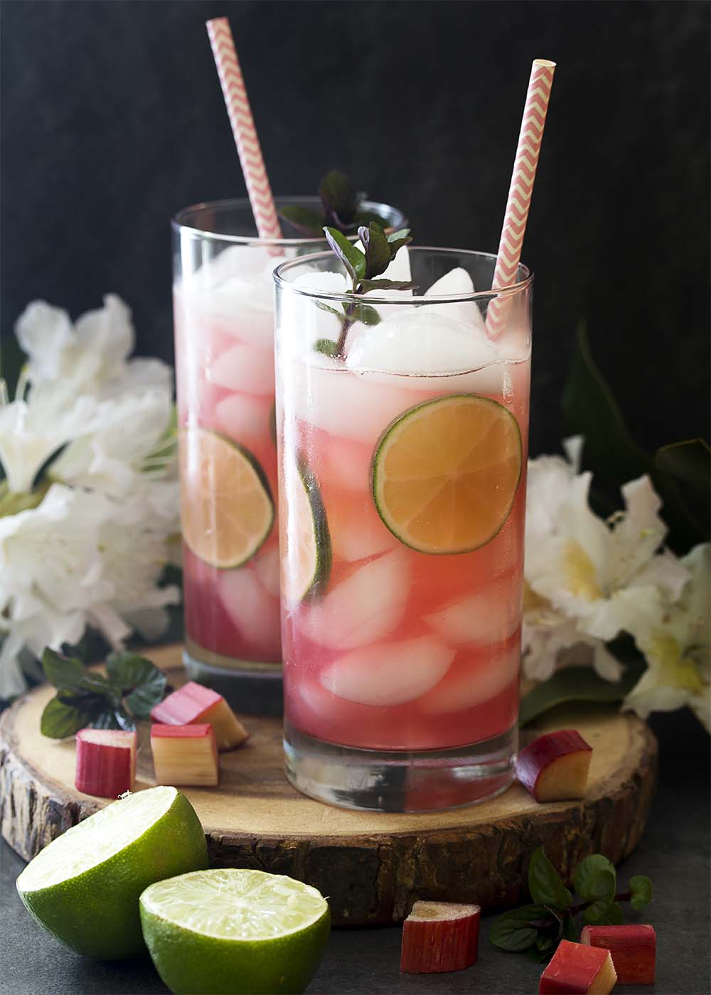 Two tall glasses of cold and fizzy rhubarb rickeys with sprigs of mint and slices of lime.