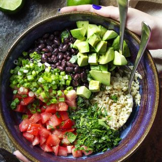For a healthy and easy summer side dish, try my Southwestern brown rice and black bean salad with tomatoes, avocados, cilantro and a spicy lime dressing. It's great warm or cold and both gluten-free and vegan as well.   justalittlebitofbacon.com #southwestern #ricesalad #summerrecipes #salads #glutenfree #vegan