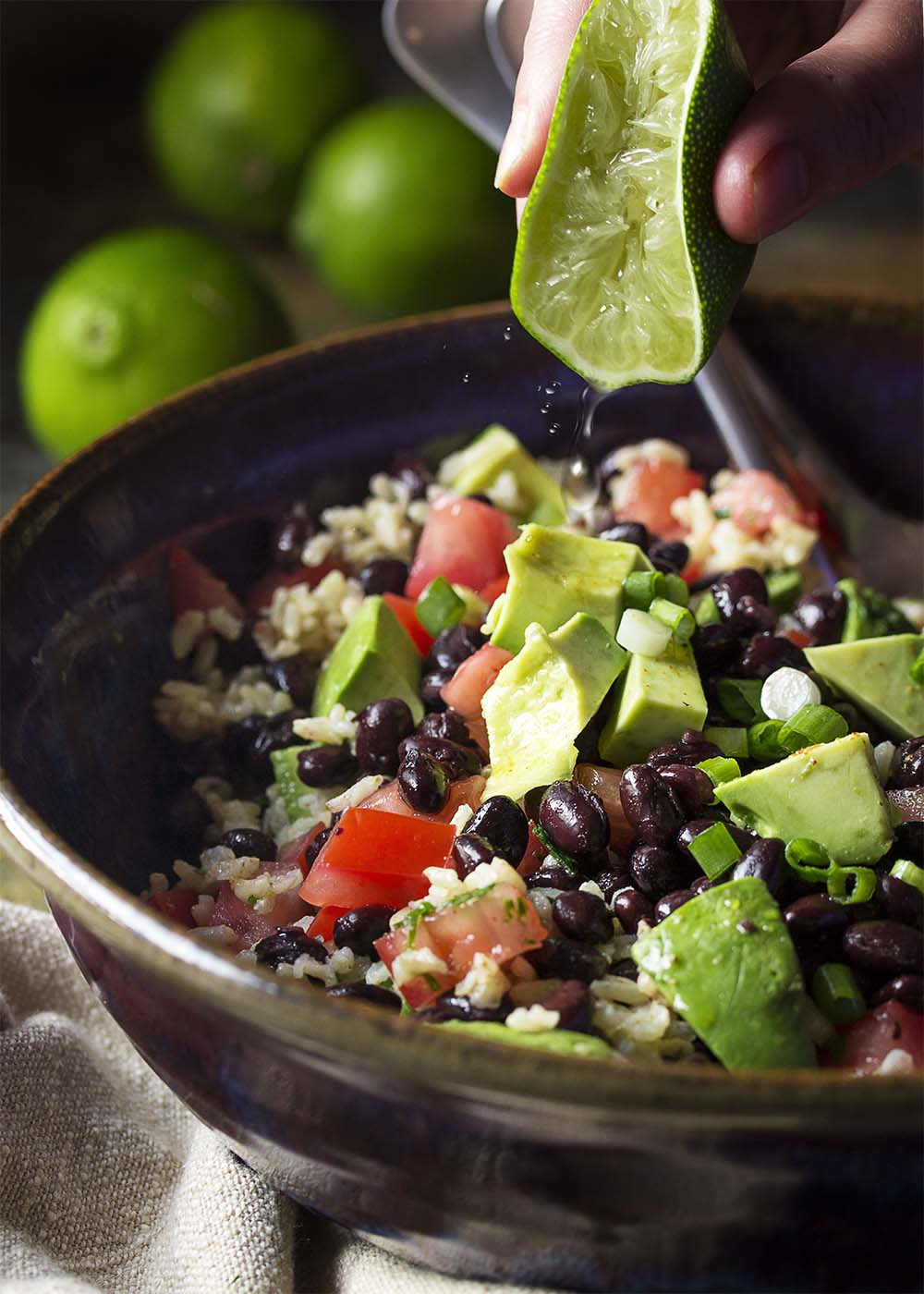 Squeezing lime into a serving bowl of salad with rice, black beans, tomatoes, and avocado.