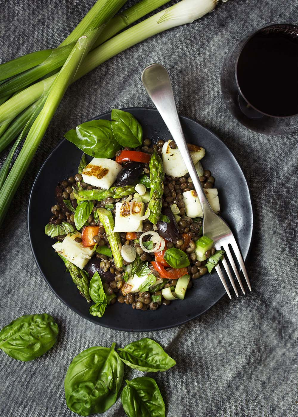 Top view of a plate of halloumi lentil salad with asparagus, bell pepper, cucumbers, and olives.
