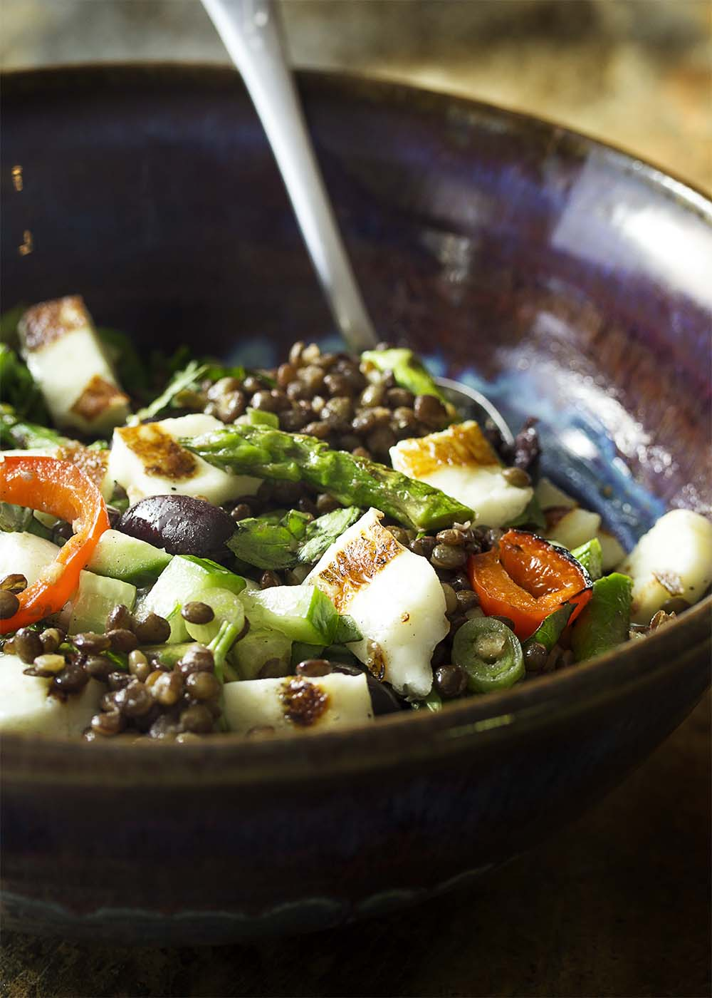 A serving bowl of grilled halloumi and French lentils tossed in a salad with vegetables and sherry vinaigrette.
