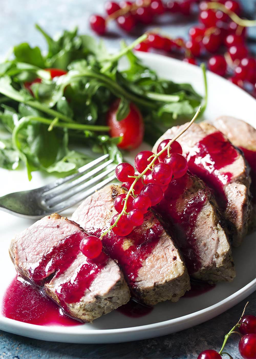 A white dinner plate with savory red currant sauce over sliced roast pork.