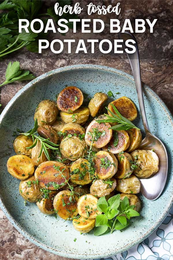 Potatoes in a serving bowl with text overlay - Roasted baby potatoes.