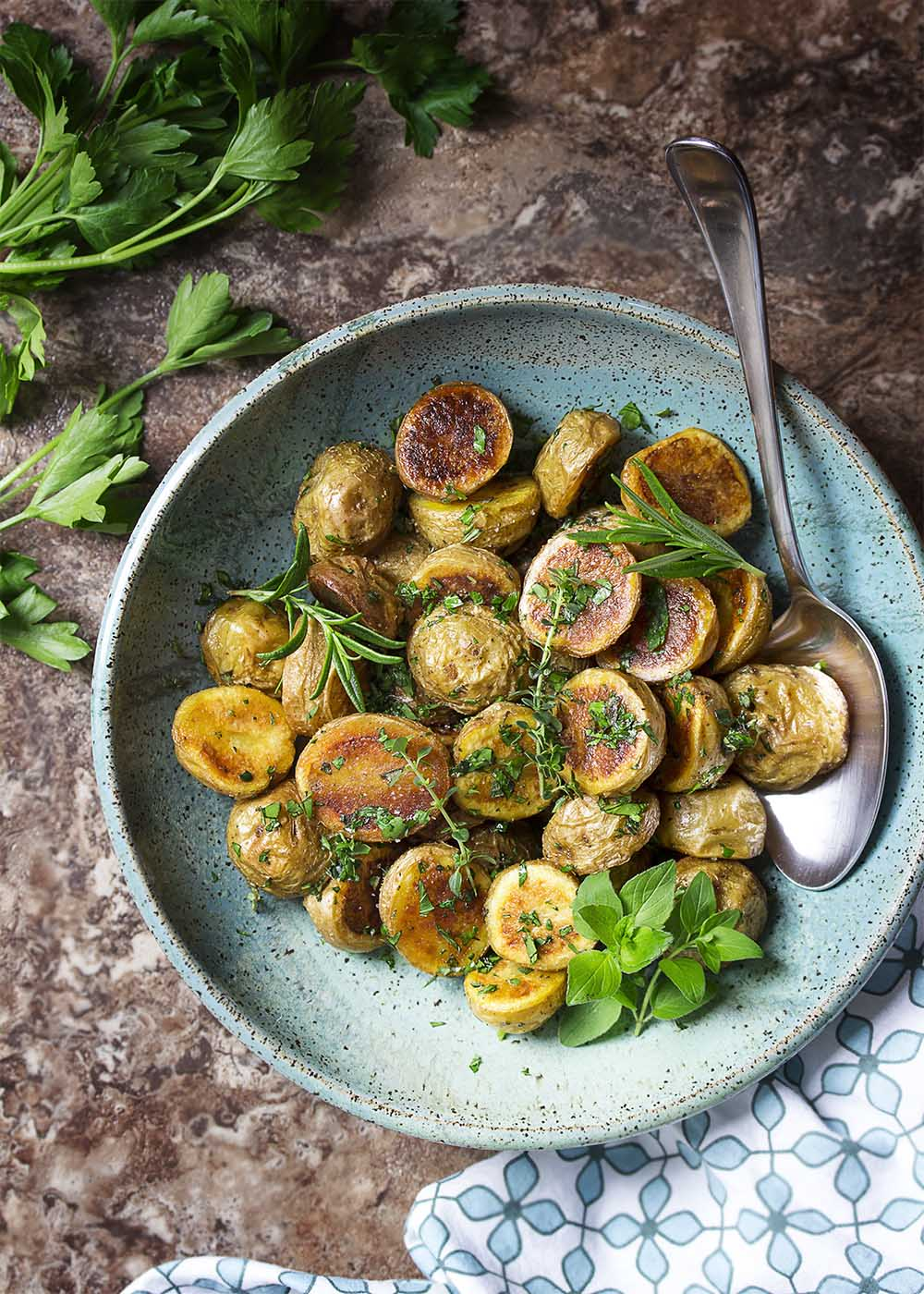 Top view of a serving dish of herb roasted potatoes with fresh herbs scattered about and a large serving spoon.