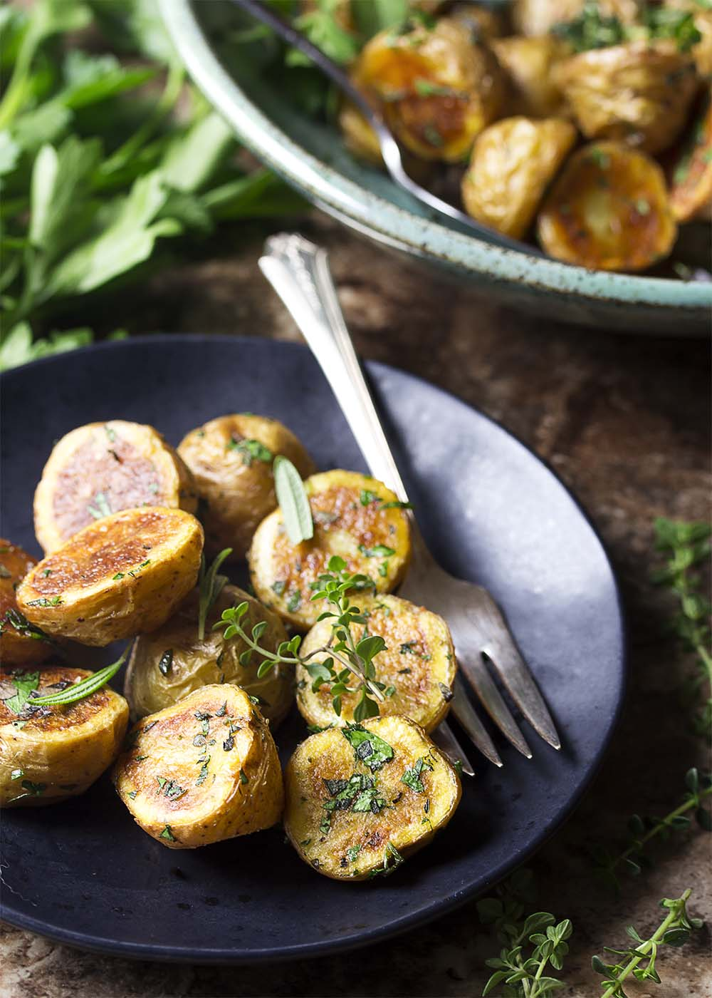 Deep golden brown crispy herbed potatoes on a plate with a fork.