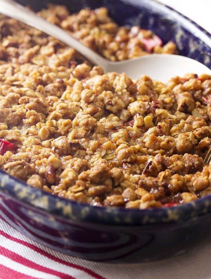 Looking for an easy fruit dessert recipe? This spiced rhubarb crisp is a simple, old fashioned dessert full of the flavors of cinnamon, ginger, and cloves and topped with an oatmeal pecan crumble! Best served with a scoop of vanilla ice cream. | justalittlebitofbacon.com #rhubarb #dessertrecipes #spring #fruitcrisp #dessert #crisp