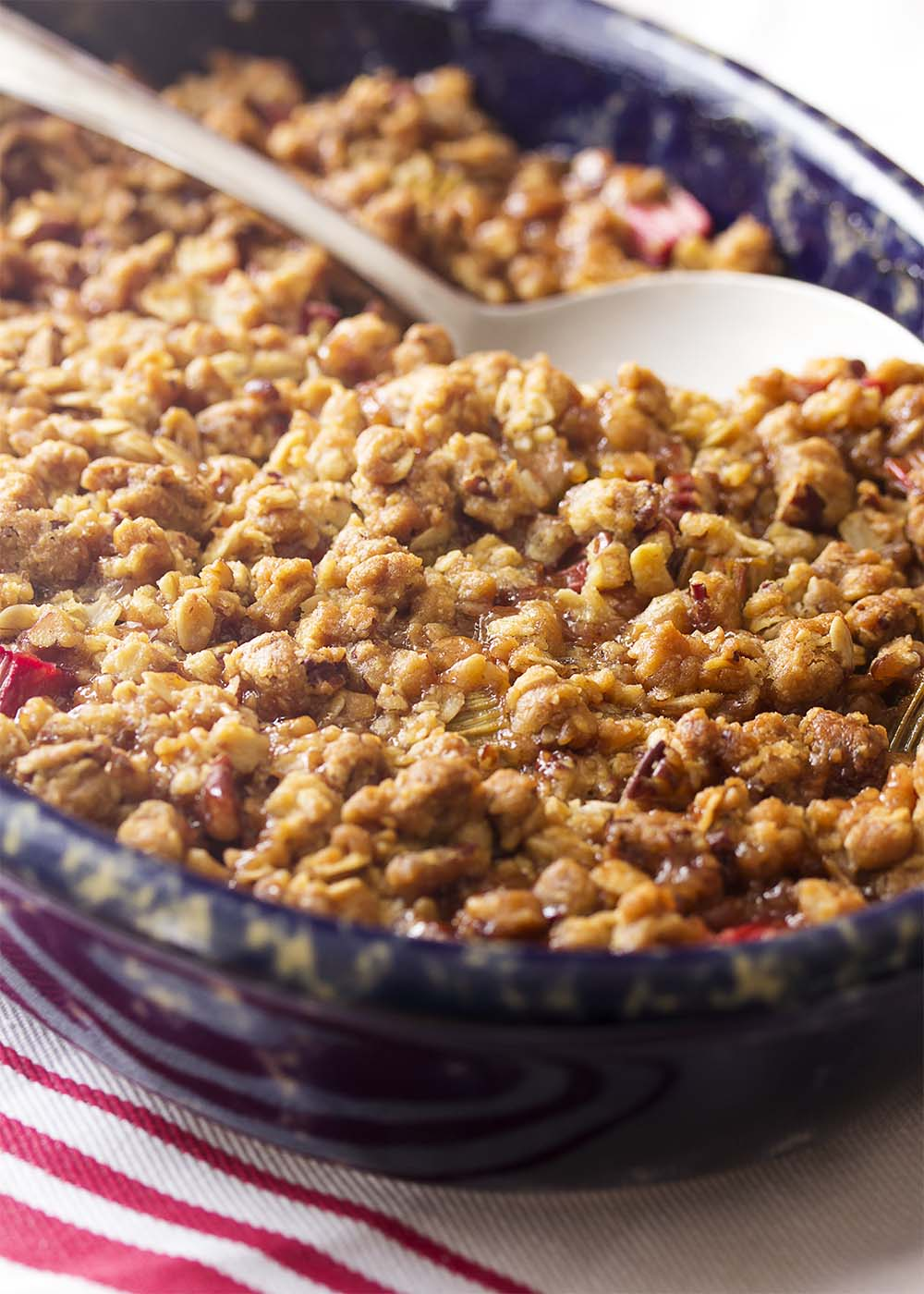 An oval gratin dish of spiced rhubarb crisp with a golden brown oatmeal pecan crumble topping.