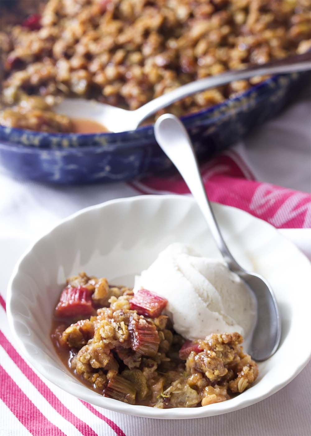 A white bowl with a scoop of vanilla ice cream, some rhubarb crisp, and a spoon.