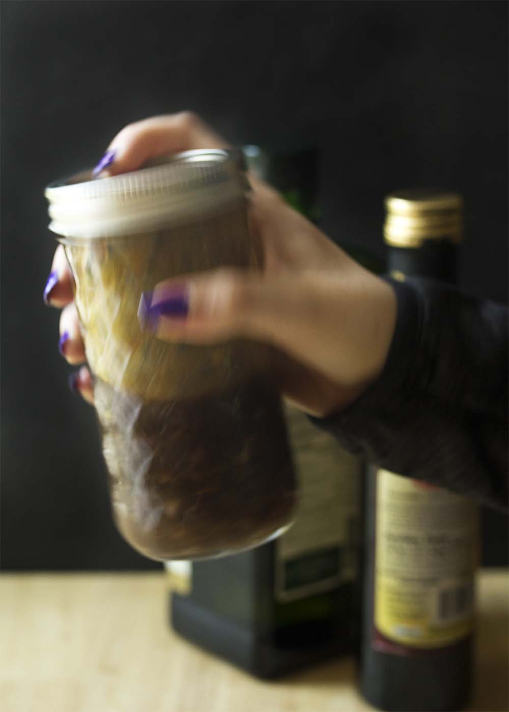 A hand shaking a mason jar filled with thick and tangy honey balsamic vinaigrette dressing.