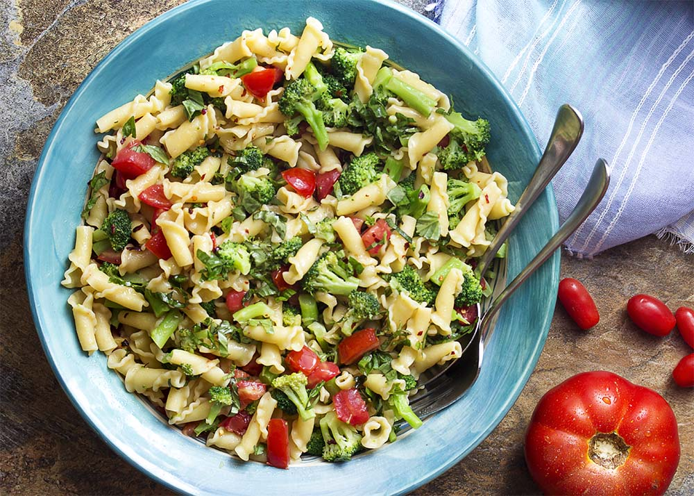 Top down view of a large serving bowl of summer farm stand pasta full of broccoli, tomatoes, and basil.