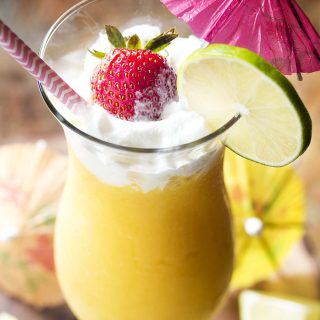 Get out your blender because it's time to make your new favorite summer party drink! This frozen mango daiquiri recipe with frozen mango, ice, lime juice, simple syrup, and rum is sweet and sour and simple to make. Top with whipped cream, fresh fruit, and slices of lime. | justalittlebitofbacon.com #summerrecipes #drinkrecipes #cocktails #drinks #daiquri #mangos