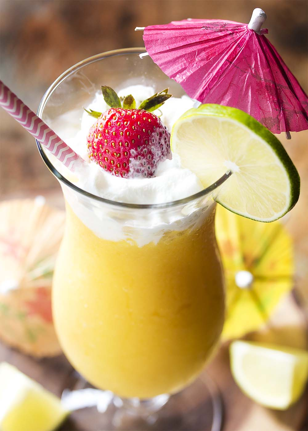 Close up of a frozen mango daiquiri with whipped cream on top and a straw and umbrella on the glass.