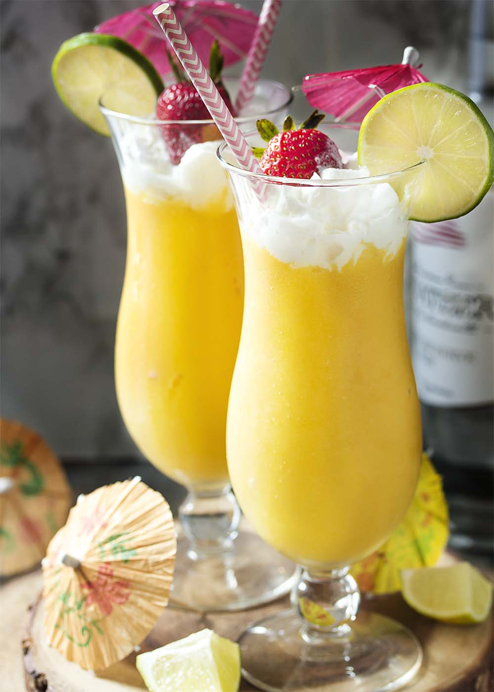Two tall glasses of frozen mango daiquiri with whipped cream and umbrellas.