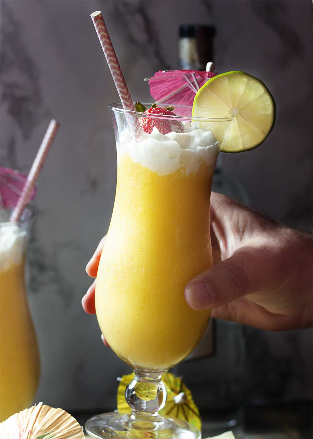 A hand lifting up a glass of mango daquiri garnished with strawberry and lime.
