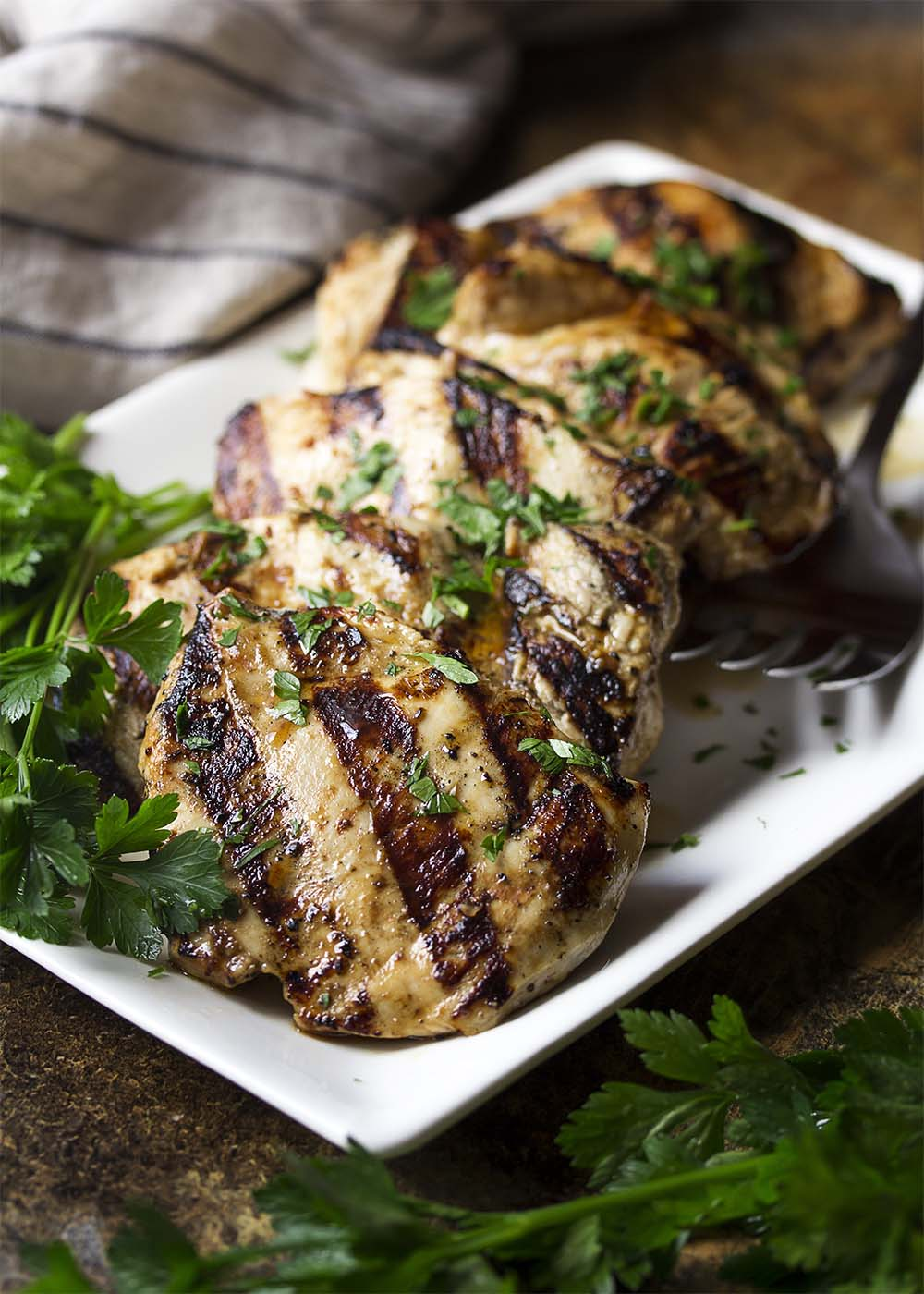 A platter of juicy and tender grilled chicken breast which has been marinated in balsamic dressing.