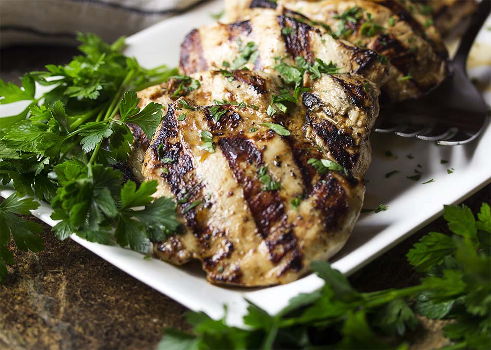 Close up of grilled chicken on a platter showing the dark grill marks.