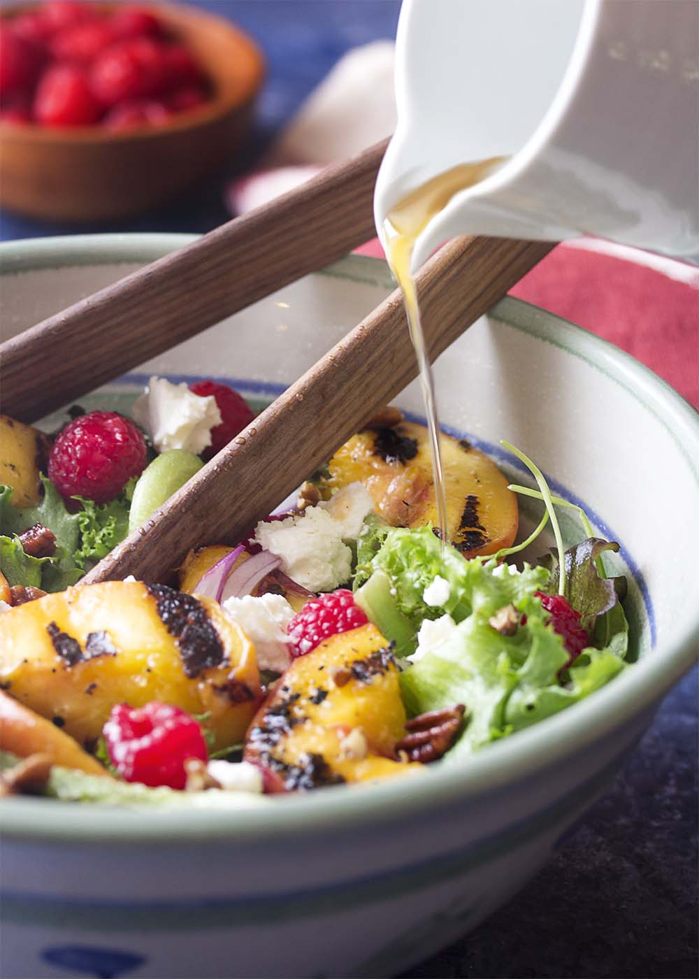 Pouring maple vinaigrette dressing into a serving bowl of sald with mixed greens, berries, and grilled peaches.