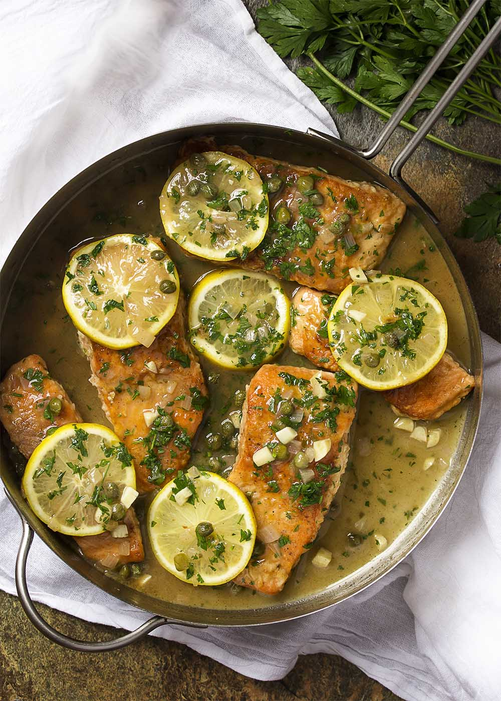 A skillet full of salmon piccata with a lemon, garlic, parsley, and caper sauce and lemon slices on top.