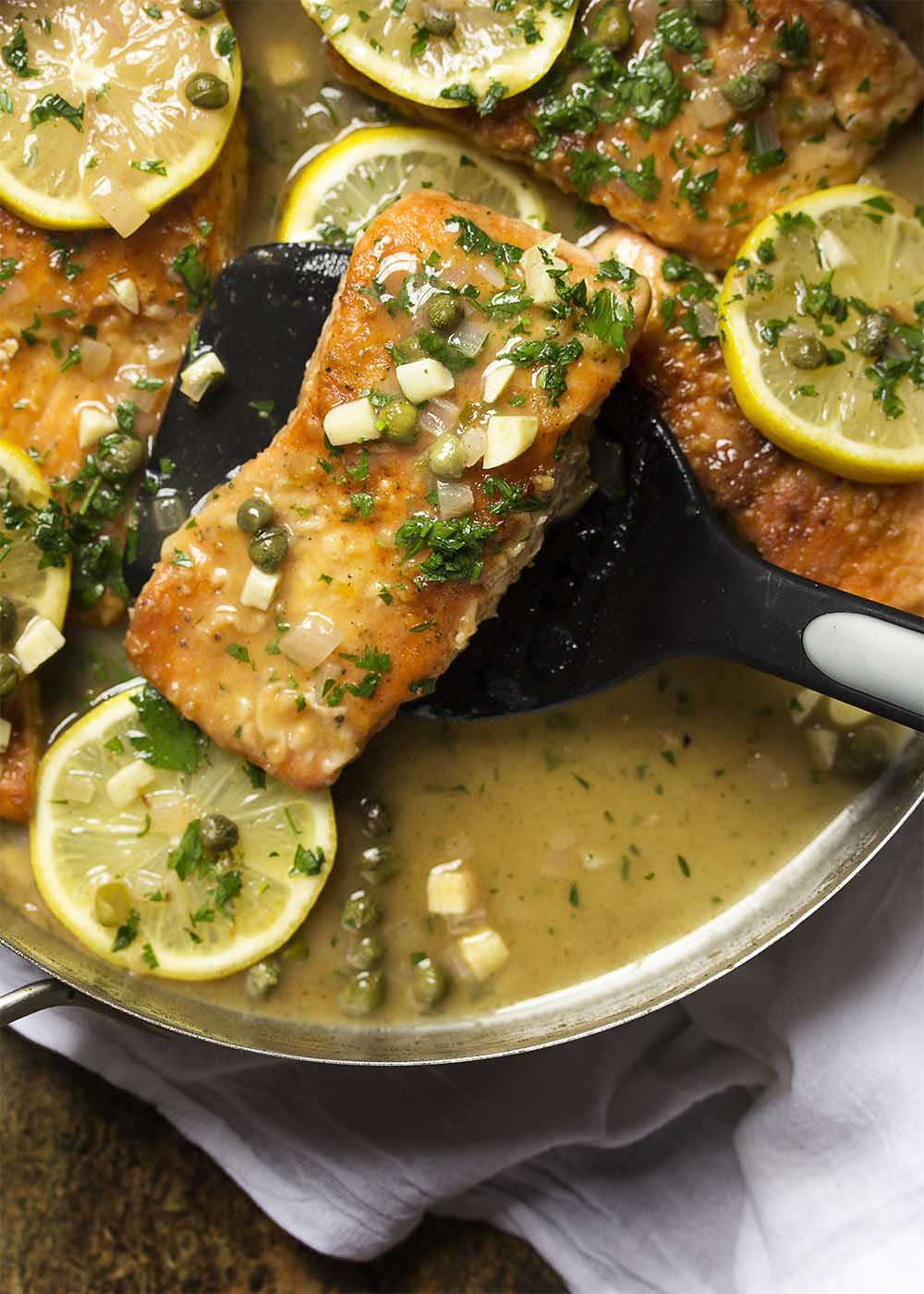 A spatula holding up a piece of salmon piccata ready to serve it onto a plate.