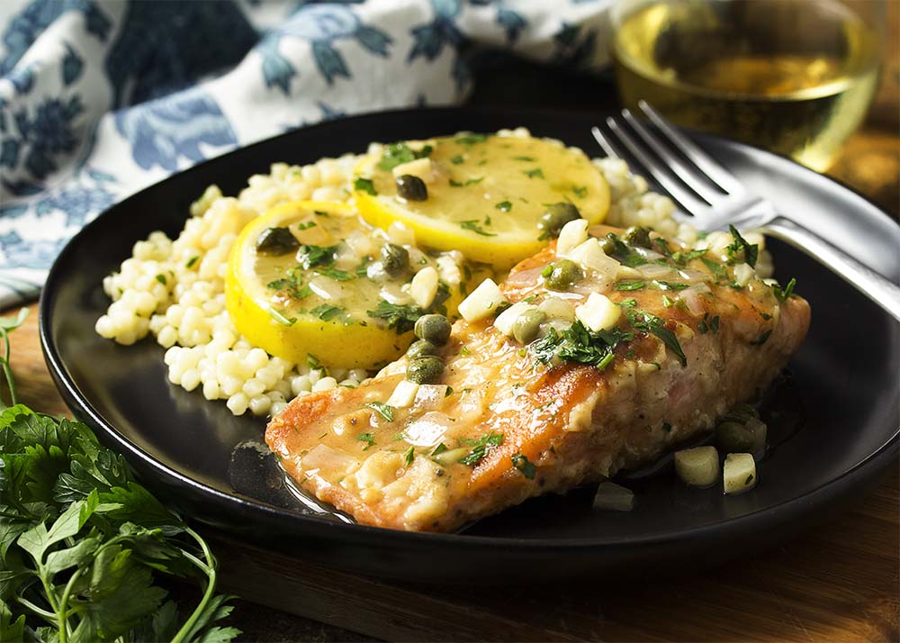 A plate with salmon piccata over pearl couscous all topped with a tangy lemon caper sauce.