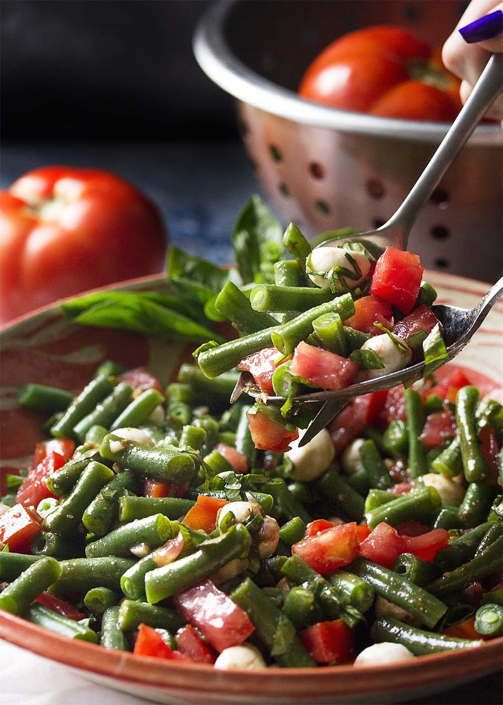 Scooping up a portion of green bean, tomato, mozzarella, and basil salad from the serving bowl.